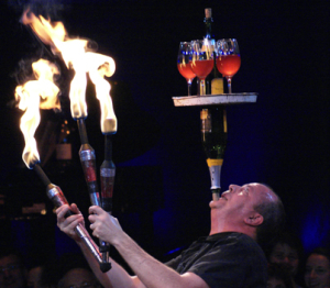 Steve juggling fire clubs, while balancing bottles and glasses on his chin.